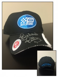 Black 6-panel baseball cap with Petty's Garage logo on front and silver Richard Petty autograph above ALI logo on brim, Back of black ball cap with Petty's Garage tagline embroidered in blue
