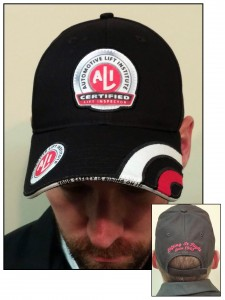 "Back of black baseball cap with red stitched lettering that says ""Lifting It Right since 1945"" above Velcro adjustment"