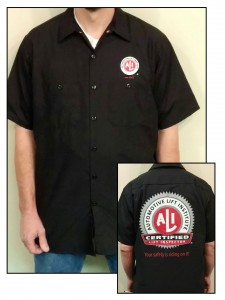 "Back view of black short sleeve work shirt with large ALI Certified Lift Inspector logo and the words ""Your safety is riding on it!"" printed in red"