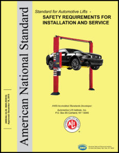 Yellow book titled Standard for Automotive Lifts – Safety Requirements for Installation and Service with black car on red two-post lift in center